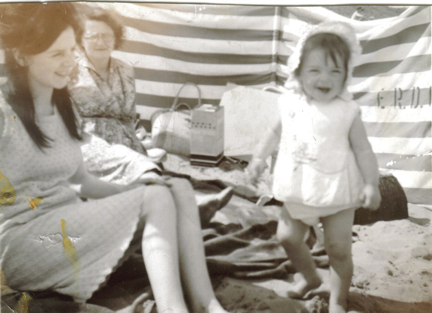 On the beach, with her mother and grandmother